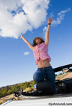 Happy ethinic woman in convertible with arms raised against a blue sky with some clouds. The Hispanic woman has her knee on the drivers headrest. She is celebrating something wonderful.
